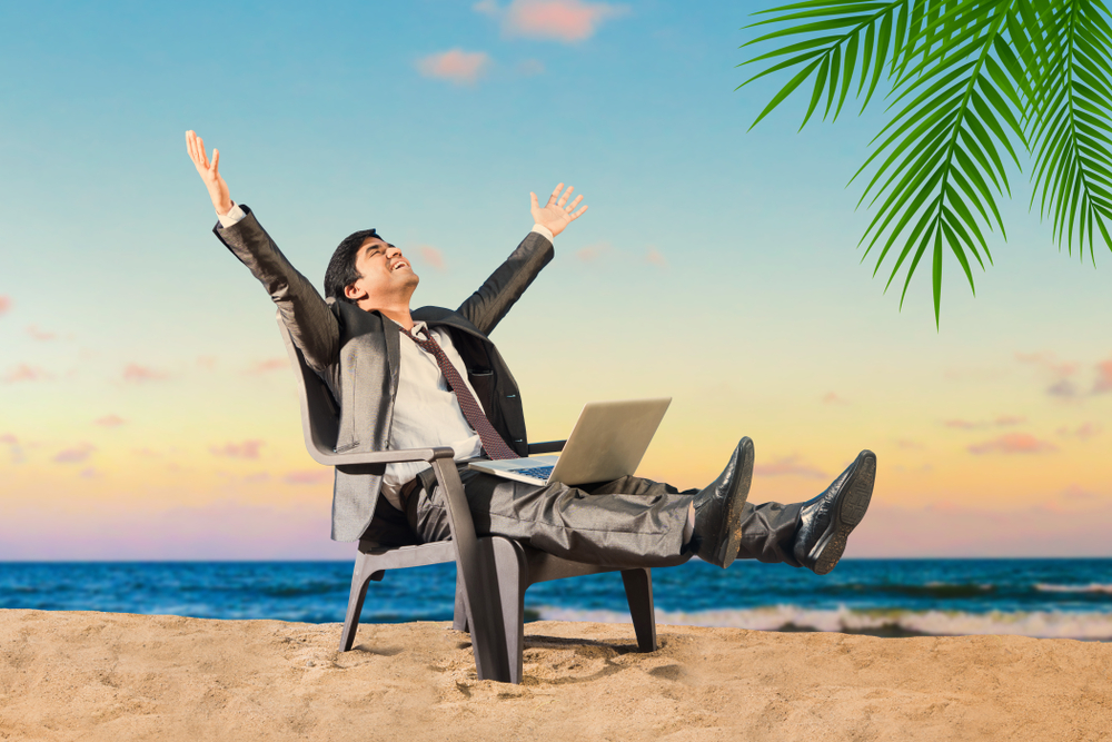 Indian/asian,Young,Businessman,At,Beach,And,Working,On,Laptop,Computer